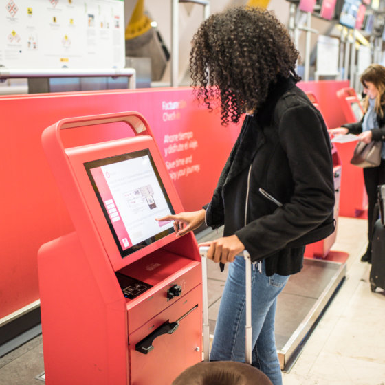 happy black woman using the check-in machine at the airport gett